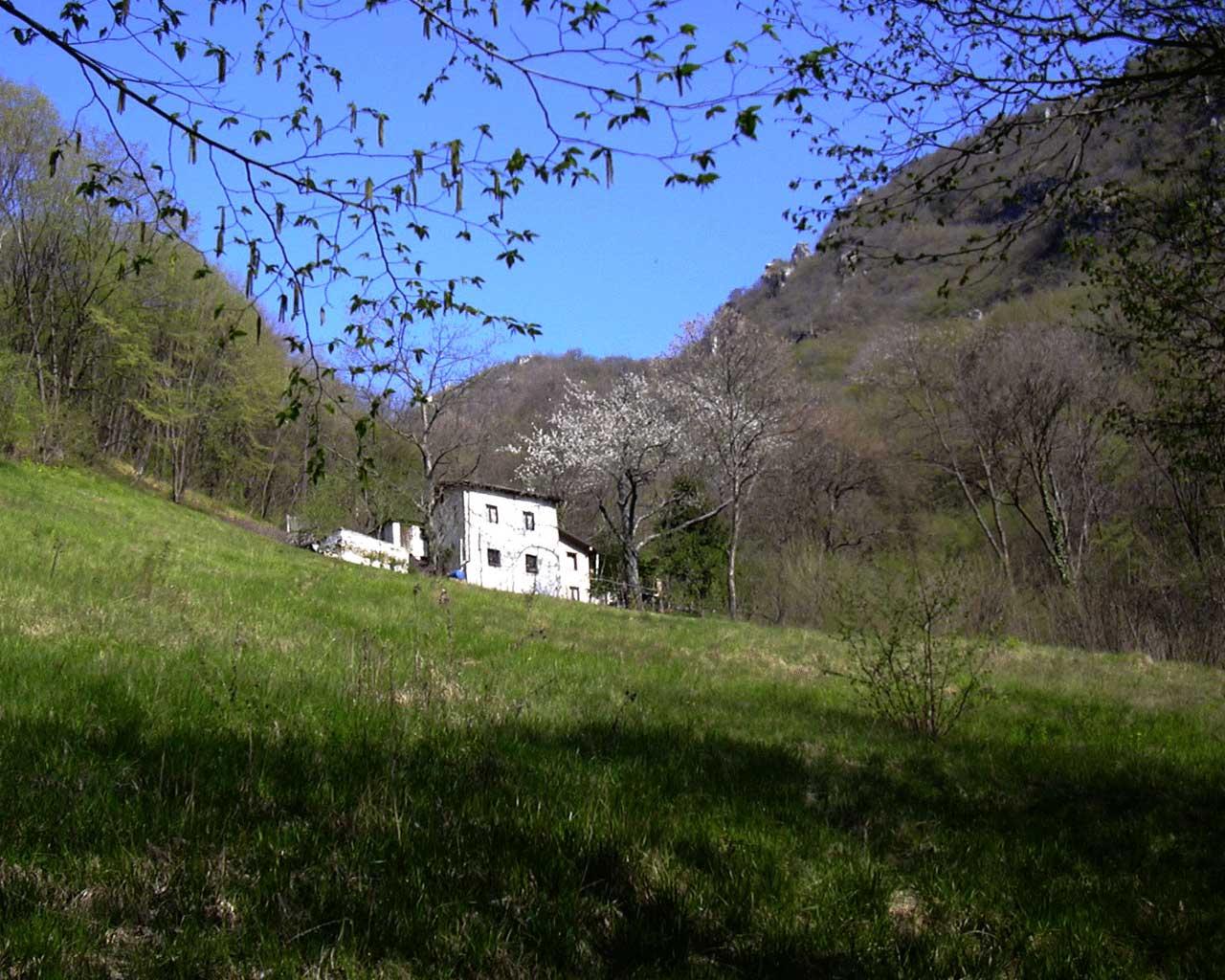 Una casa bianca e un prato verde sulla sinistra del sentiero in Valle della Murra