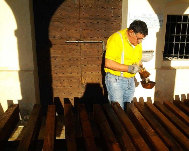 Il volontario Ermido mentre vernicia le nuove panche