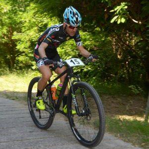 Un concorrente in sella alla sua mountain bike lungo la carrabile della Passata