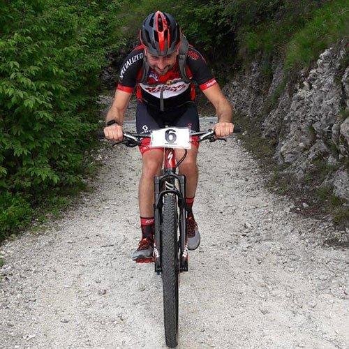 Un ciclista in sella alla mountain bike su una strada sterrata di montagna