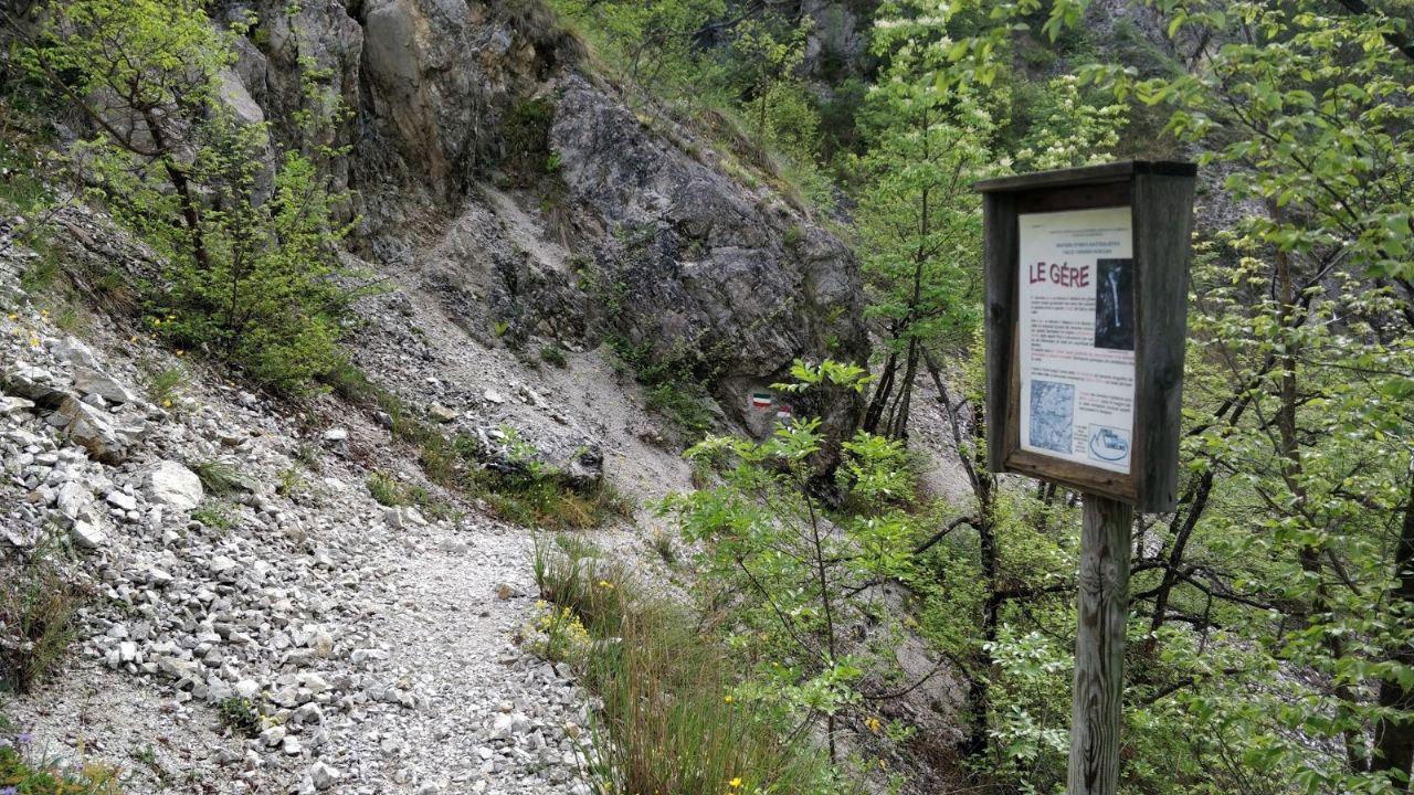 Sentiero ghiaioso e bacheca indicativa di legno