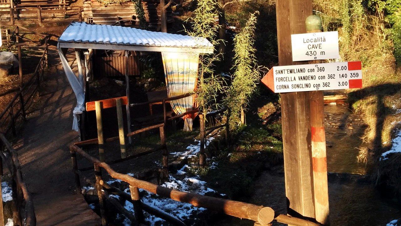 Ponticello in legno, chiazze di neve e cartelli Cai