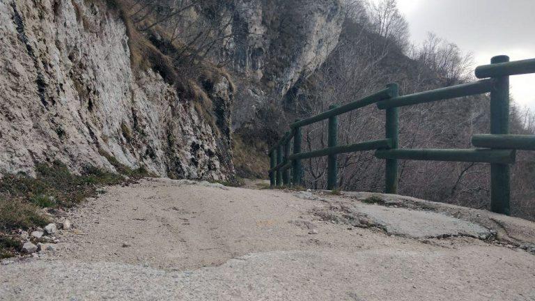Strada sterrata in discesa con recinzione di legno