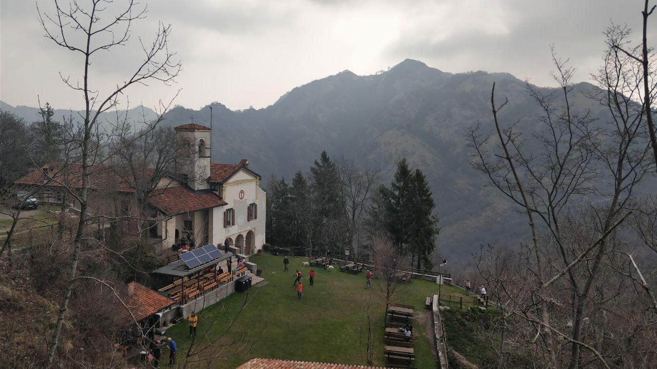 Alberi spogli e santuario di montagna sullo sfondo