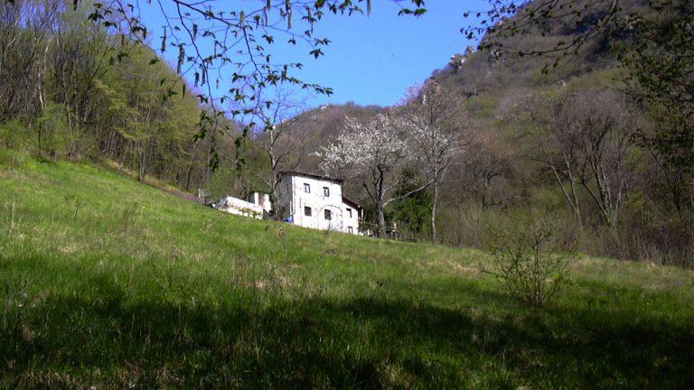 Prato estivo e casa bianca di montagna