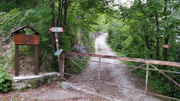 Sbarra abbassata e cartello segnavia su strada sterrata di montagna